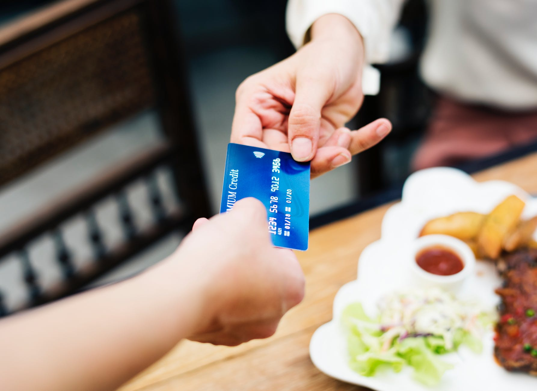 two person holding credit card closeup photo